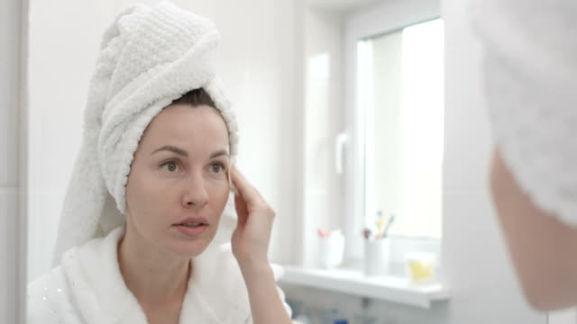 woman cleaning skin with a cotton pad removing makeup shot on red epic - cotton ball stock videos & royalty-free footage