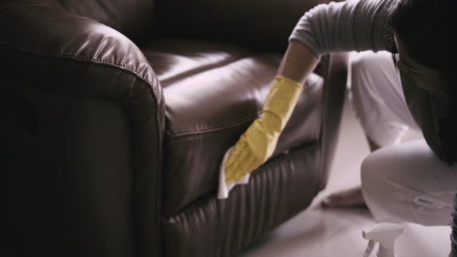 woman cleaning sofa chair protect covid-19 - armchair stock videos & royalty-free footage