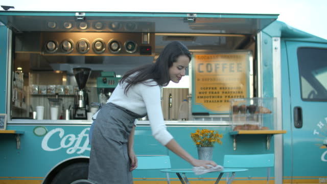 woman cleaning tables on front of coffee truck - apron stock videos & royalty-free footage