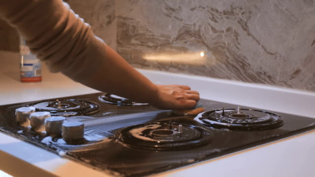 woman cleaning the stove with a sponge and foam - kitchen worktop stock videos & royalty-free footage