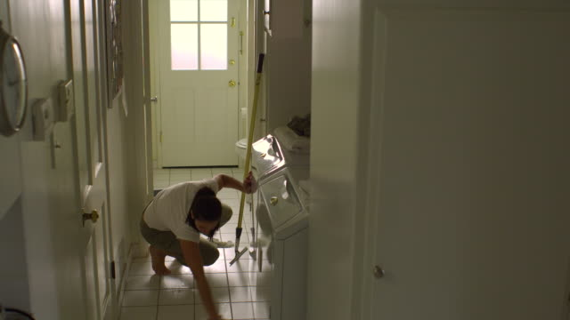 stockvideo's en b-roll-footage met ws, pan, woman cleaning tile floor in laundry room, hollywood, california, usa - betegelde vloer
