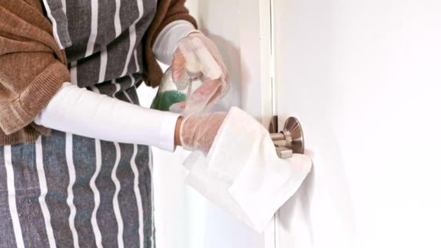 vidéos et rushes de la femme nettoie la poignée de porte pendant covid-19 - faire le ménage