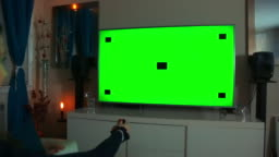 Woman Clicking Remote Button - TV Green Screen - Night - Dolly Shot