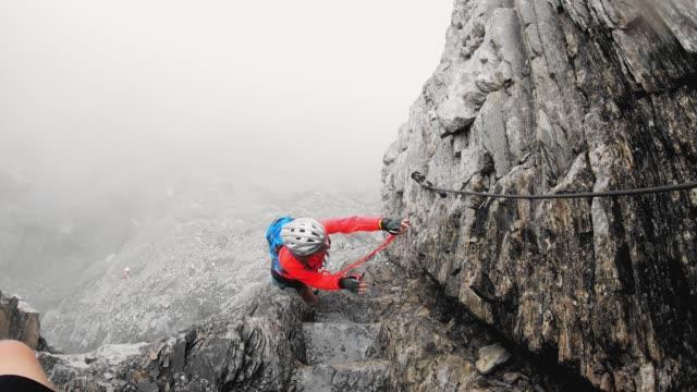 vidéos et rushes de femme grimpeur montant vers le haut de la montagne sur le sentier de via ferrata - vertige