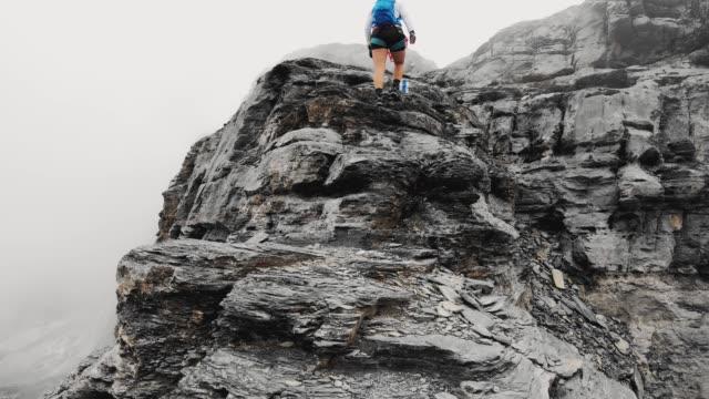 vidéos et rushes de grimpeur de femme vers le haut dans les montagnes un matin brumeux - vertige