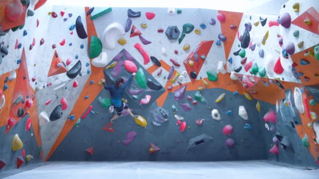 vídeos y material grabado en eventos de stock de slo mo ld mujer escalando una pared en un gimnasio de escalada interior - escalada libre