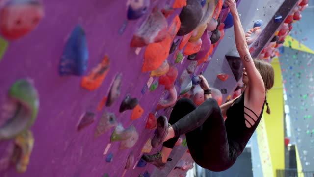 woman climbing artificial wall - solo ragazze video stock e b–roll