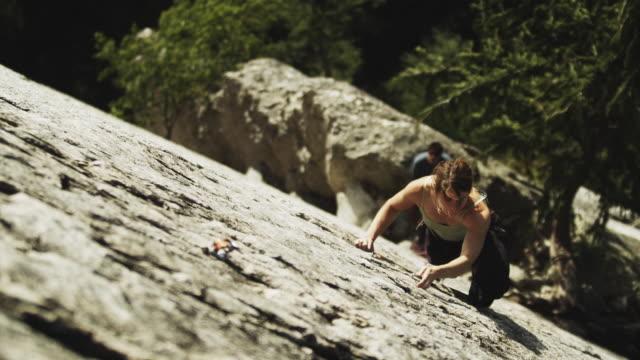 vídeos de stock, filmes e b-roll de selective focus ms ha  woman climbing cliff, attaching carabineer onto grappling hook in rock, squamish, british columbia, canada - corda de escalada