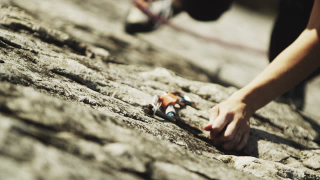 selective focus cu ha  woman climbing cliff, attaching carabineer onto grappling hook in rock, squamish, british columbia, canada - 表情点の映像素材/bロール