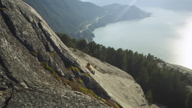 ws pan ha woman climbing cliff, lake with mountains in background, squamish, british columbia, canada - squamish stock videos & royalty-free footage