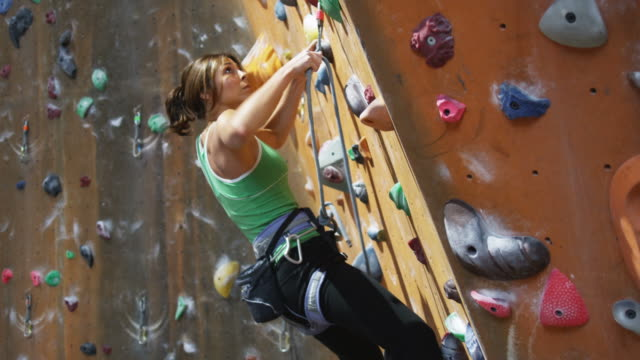 woman climbing on an indoor climbing wall - kletterwand kletterausrüstung stock-videos und b-roll-filmmaterial