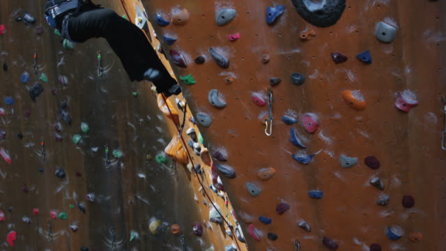 woman climbing on an indoor climbing wall