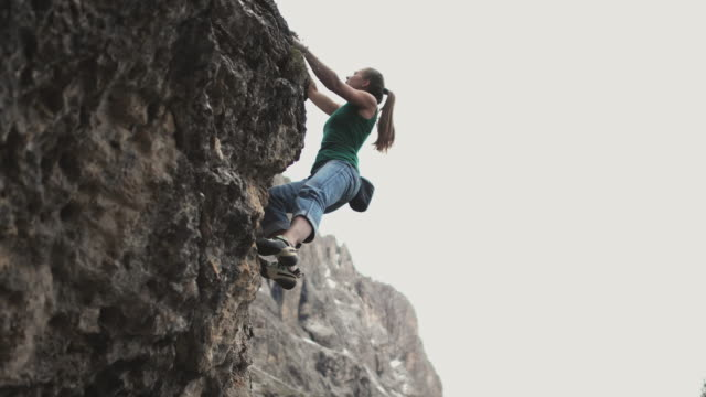 woman climbing on rock structure against clear sky - rock climbing stock videos & royalty-free footage
