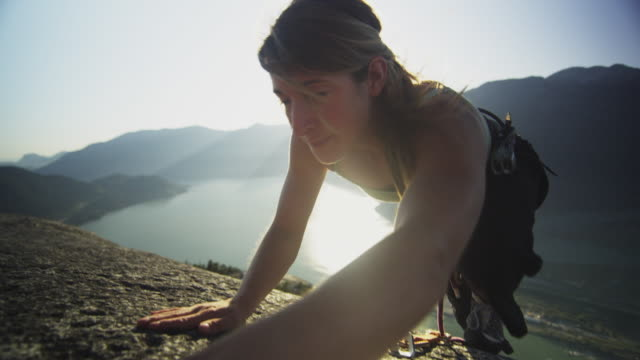 ms ws woman climbing onto top of rock cliff, lake with mountains in background, squamish, british columbia, canada - on top of stock videos & royalty-free footage