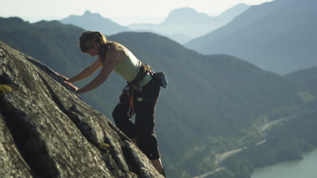 MS PAN Woman climbing rock cliff, lake with mountains in background, Squamish, British Columbia, Canada