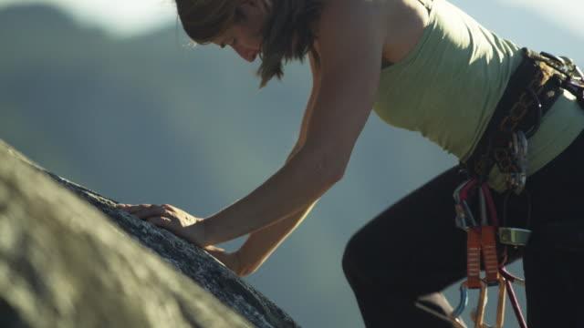 vídeos de stock, filmes e b-roll de ms selective focus tu woman climbing rock cliff, lake with mountains in background, squamish, british columbia, canada - corda de escalada