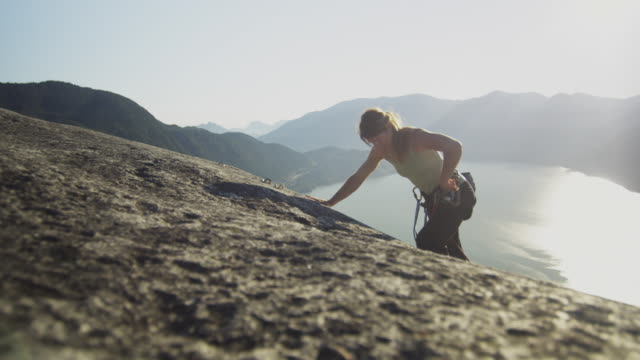 ms ha pan woman climbing rock cliff, lake with mountains in background, squamish, british columbia, canada - ganz oben stock-videos und b-roll-filmmaterial