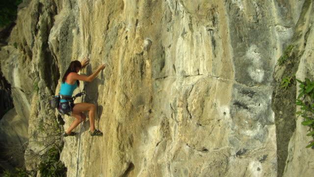 ws woman climbing rock face/ krabi, thailand - railay beach stock videos and b-roll footage