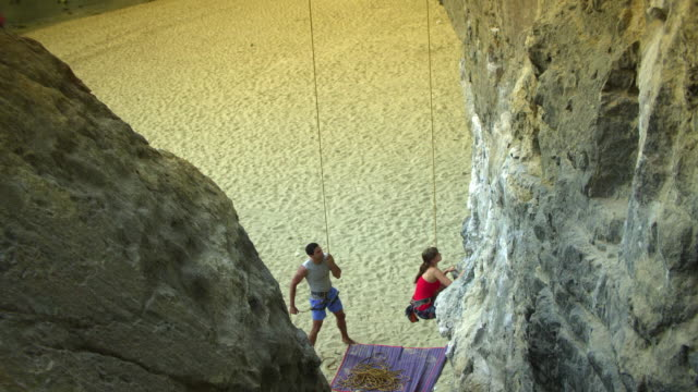 ha ms woman climbing rock face, man belays on beach below / krabi, thailand - rock face stock videos & royalty-free footage