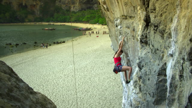 ms woman climbing rock face, man standing on beach belaying, woman falling / krabi, thailand - rock face stock videos & royalty-free footage