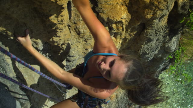 cu woman climbing rock faceascending, looking up and smiling / krabi, thailand - railay beach stock videos and b-roll footage