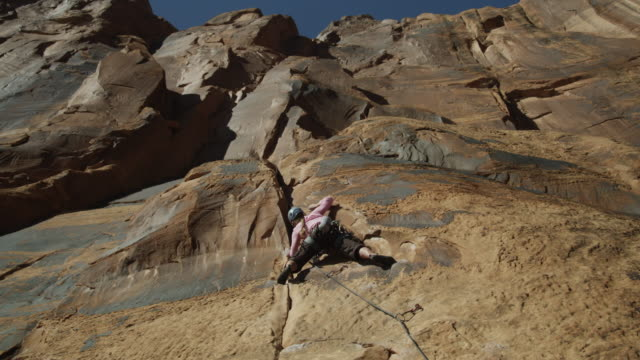 ws ds woman climbing rock / moab, utah, usa - felsklettern stock-videos und b-roll-filmmaterial