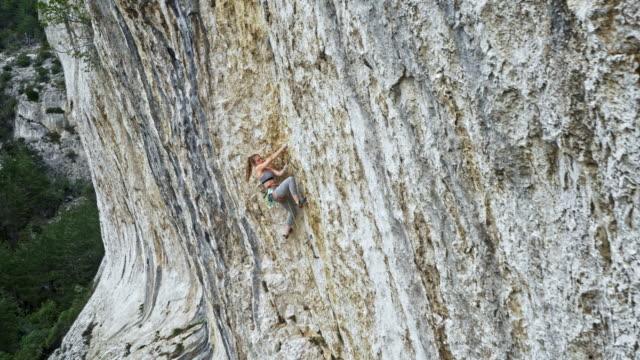 AERIAL femme grimper sur une falaise