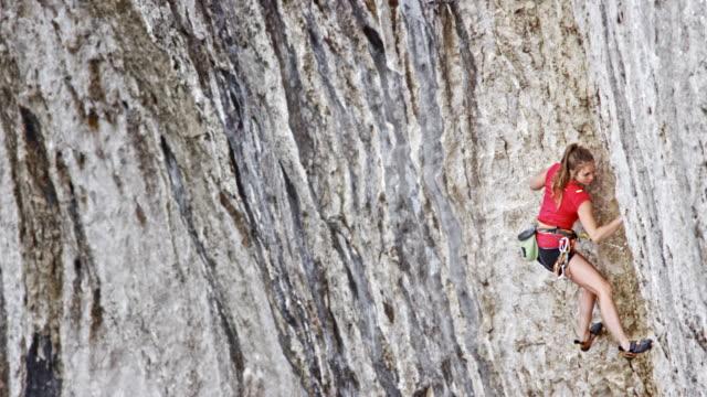 pan-frau klettern auf einer klippe - felsklettern stock-videos und b-roll-filmmaterial
