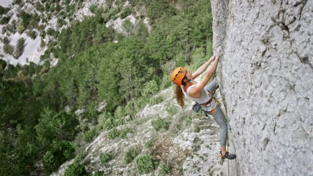 woman climbing up a cliff - rock climbing stock videos and b-roll footage
