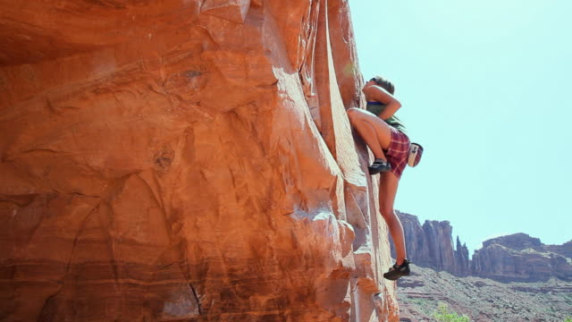 ws tu woman climbing up boulder / moab, utah, usa - rock face stock videos & royalty-free footage