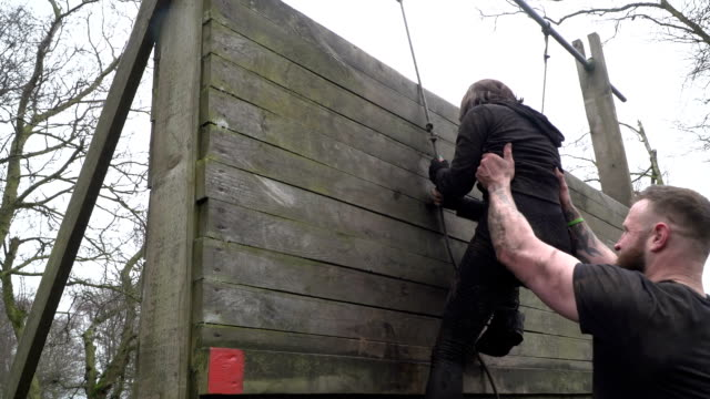 Woman climbing up rope wall on Assault Course / Obstacle course - Slow Motion