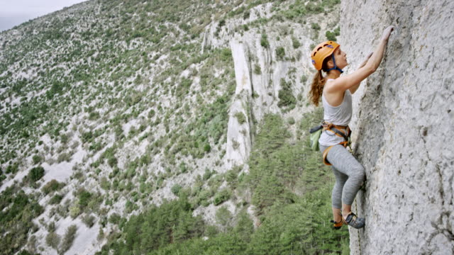 woman climbing up the rocky wall of a cliff - rock climbing stock videos & royalty-free footage