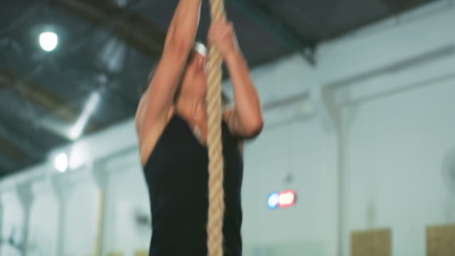 ms a woman climbs a rope in a gym / rio de janeiro, brazil - 不完全な美しさ点の映像素材/bロール