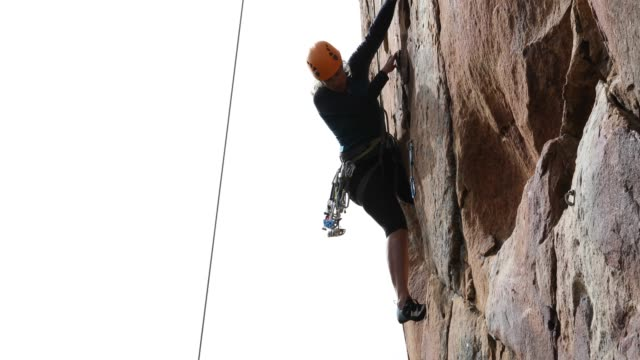Woman climbs difficult, overhanging rock wall