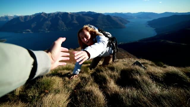 Woman climbs mountain range, hand reach out to help