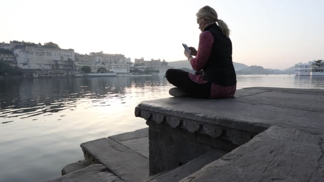woman climbs onto ghat above lake and floating palace - see other clips from this shoot 56 stock videos & royalty-free footage