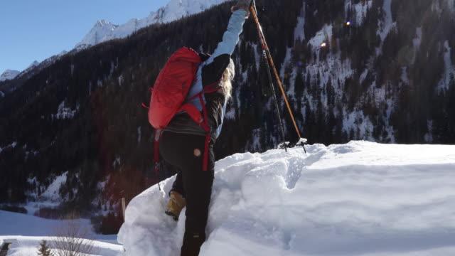 woman climbs onto snow summit - ski jacket stock videos & royalty-free footage