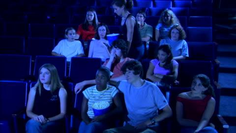 a woman climbs over people as she returns to her seat with popcorn during a movie. - biosalong bildbanksvideor och videomaterial från bakom kulisserna