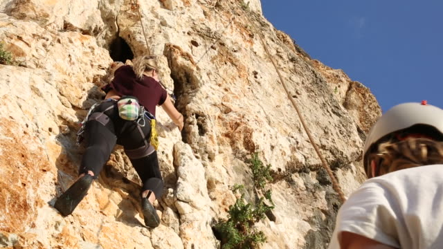 woman climbs sheer rock face while teammate belays - rock face stock videos & royalty-free footage