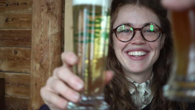 woman clinking beer glasses with her partner - einen toast ausbringen stock-videos und b-roll-filmmaterial