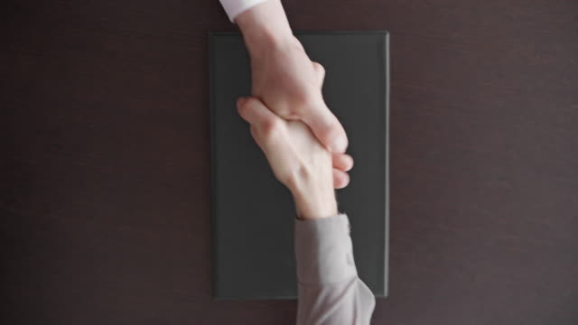 woman closes a file with a contract and shakes hands with a businessman - handshake stock videos & royalty-free footage