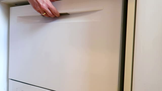 woman closing a dishwasher - stock video - lavastoviglie video stock e b–roll