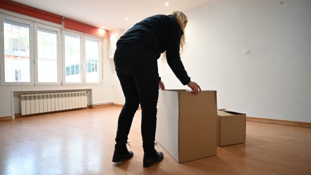 woman closing and then pushing a cardboard box. moving - one mature woman only stock videos & royalty-free footage