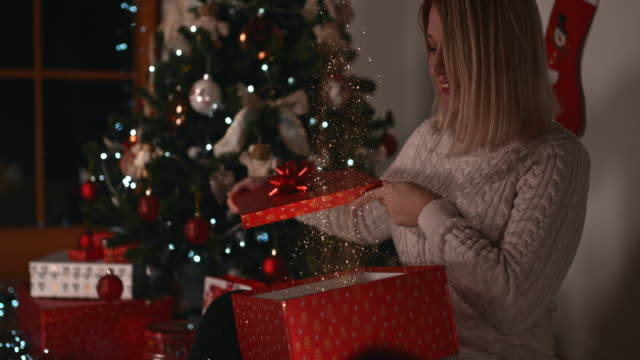 slo mo woman closing her christmas present after glittering golden dust stop blowing out - advent stock videos & royalty-free footage
