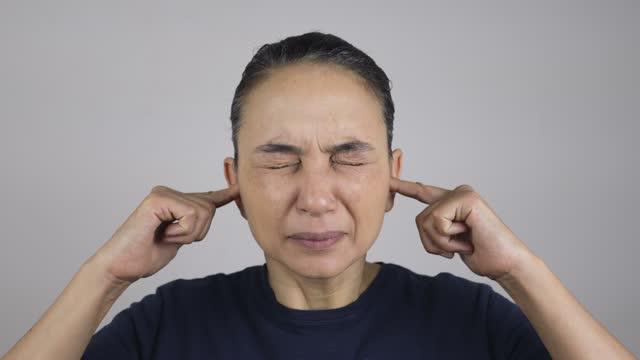 vidéos et rushes de femme fermant ses oreilles avec des doigts - tête composition