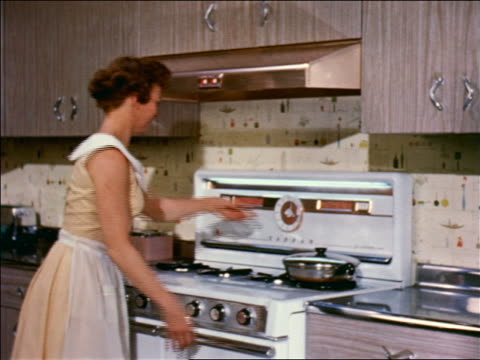 vidéos et rushes de 1959 woman closing oven door, setting timer + walking away in kitchen / industrial - prelinger archive
