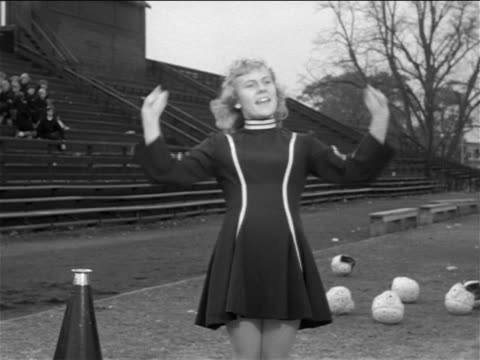 b/w 1953 woman coach in cheerleading outfit practicing cheerleading routine / documentary - cheerleader stock videos & royalty-free footage