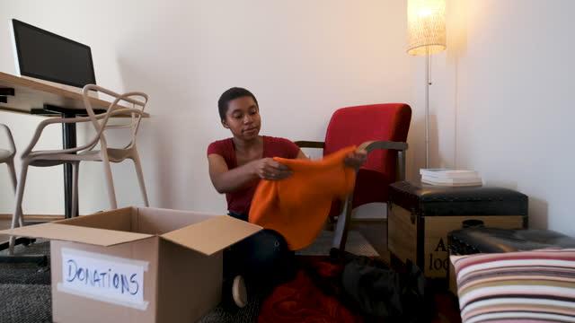 vídeos y material grabado en eventos de stock de mujer colaborando con ropa para la donación - sólo mujeres jóvenes