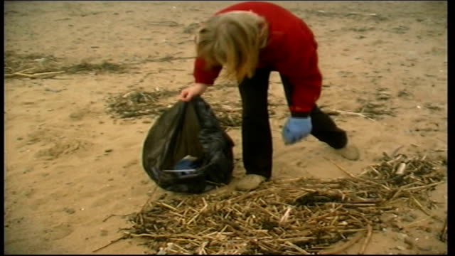 woman collecting rubbish from beach england somerset weston super mare ext woman with black bin liner collecting rubbish from beach / more ditto /... - weston super mare stock videos and b-roll footage