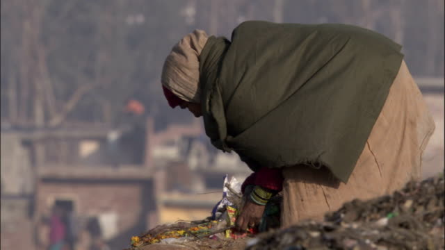 woman collecting rubbish on tip available in hd. - picking up stock videos & royalty-free footage
